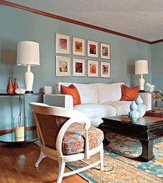 living rooms - white sofa blue walls orange silk pillows black asian table blue orange rug  Inspiration Family Room ~ I love the blue and orange!