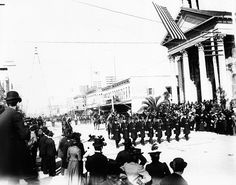 California Jubilee Parade.       Members of the San Jose Police Department march past the Pacific Hotel and Saint Joseph's Roman Catholic Church. The Electric Light Tower can be seen in the background.         Collection: Historic Photograph Collection (SJPL California Room).  Date: December 21, 1899.