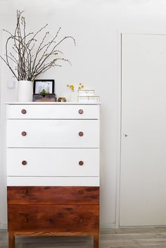 A Cup of Life made 3 simple changes to this plain IKEA dresser…she painted 3/4's of the piece white…stained the bottom section and added stained hardware…the results? Mid Century Modern Magic!