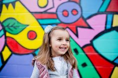 Fun, colorful portrait of a young girl (all smiles!) at a public art mural in Portland, OR. Photographed by Steadfast Studio.