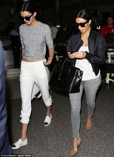 A true sister act: Kim Kardashian (R) and Kendall Jenner coordinated their looks at LAX airport on Thursday