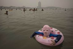 A Chinese girl wears a face-kini to protect her from jellyfish stings, algae and the sun's ultraviolet rays as she floats in the water on the Yellow Sea in Qingdao, China, Aug. 21, 2014.  Kevin Frayer—Getty Images