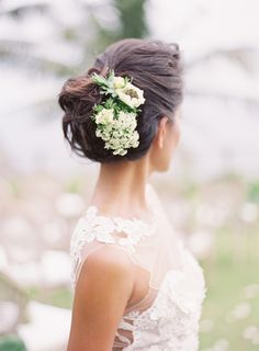 Elegant low bun flower embellished wedding hairstyle: http://www.stylemepretty.com/2017/04/27/tropical-wedding-inspiration/ Photography: Oliver Fly - http://oliverfly.com/