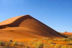 Rote Sandberge Die Sanddünen der Namib in Namibia sind von Wasser und Wind aufgehäufte Überreste eines kleingemahlenen Gebirges und mit 350 Metern Höhe die höchsten Sandhaufen der Erde. Die orange-rote Farbe kommt vom hohen Eisenoxidanteil: Die Namib rostet