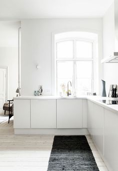 Bright open plan dining room with L shape countertop in Christianshavn. Photo by Frederikke Heiberg. #diningroom #whitewall