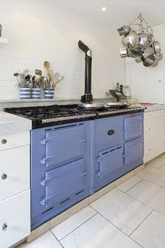FARMHOUSE – INTERIOR – vintage early american farmhouse showcases raised panel walls, barn wood floor, exposed beamed ceiling, and a simple style for moulding and trim, like in this farmhouse kitchen with a scrumptious colour aga stove and oven.