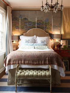 A six-panel chinoiserie screen provides visual interest behind the headboard. - Traditional Home ® / Photo: Colleen Duffley / Design: Megan Rice Yager