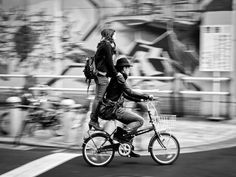 Bicycle Ride, Japan Photograph by Sun Jie, My ShotA couple riding a bicycle in front of me, Shinsaibashi, Osaka  What Makes This a Photo of the Day? Many times what makes a photograph special are the small details that you don't notice right away. I was first drawn to this photograph by the moment captured—part of the blur of city life. But what I love most are the high-heeled shoes worn by the woman perched on the back of the bicycle. —Alexa Keefe, Photo of the Day editor