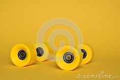 Four yellow rollerskate wheels on a yellow background