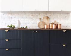 Dark blue-black, dark wood coutnertop, white top cabinets, brass hardware. Yes.