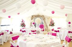 Brighten a white marquee with bold coloured paper lanterns and coloured ribbons. Neutral table decor adds to the beach theme: http://www.hanginglanterns.co.uk/colour/pinks-purples
