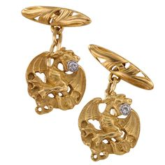 Art Nouveau Diamond Gold Griffin Cufflinks. Art Nouveau Griffin Cuff Links With Diamonds A pair of three dimensional fierce griffins executed in great detail, completed by back supports embellished with classic organic motifs prevalent in Art Nouveau jewels. The matching designs feature a pair of old European-cut diamonds totaling approximately 0.10 carat, mounted in 18 karat yellow gold, overall diameter approximately 3/4 of an inch. Circa 1905.