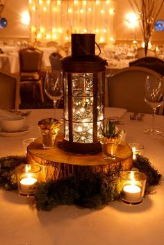 Wooden slice table centre with moss, succulents, votives and a copper lantern with pealights for a woodland wedding table centre by www.stressfreehir… - Wooden slice table centre with moss, succulents, votives and a copper lantern wi. Lighted Centerpieces, Lantern Centerpiece Wedding, Wedding Lanterns, Centerpiece Ideas, Wooden Wedding Centerpieces, Wood Slice Centerpiece, Lantern Table Centerpieces, Winter Centerpieces, Fairy Lights Wedding