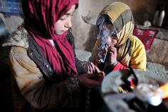 The Children of Crystal Farzana, 11, help her sister, Jamila, 7, to smoke crystal, a very pure heroin made in Afghanistan. Both say that if they don't use heroin for one day, they feel pain in their body. Their parents went to beg in the city and left them with drugs to spend the day quietly. Addiction among children is widespread in Afghanistan as there is a strong belief that opium is a medicine. 30 years of war have made Afghanistan a narco-state.