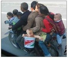 Family on a motorcycle; baby in a bucket.