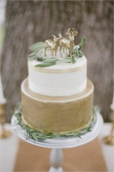 gold and white wedding cake with ribbon accents #weddingcake #goldcake #weddingchicks http://www.weddingchicks.com/2014/01/20/boho-garden-wedding/