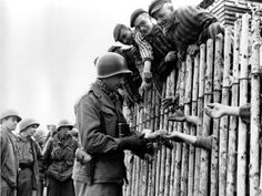 This documentary film still shows an American G.I. reaching out to outstretched hands of inmates of the liberated Nazi concentration camp at Dachau, West Germany, in April 1945 during World War II.