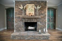 The fireplace is flanked by twin arched wood doors, painted blue-green and distressed. The fireplace is resurfaced in dry stack stone, replacing a standard brick hearth and surround.