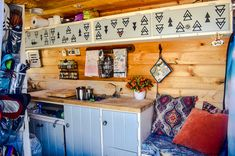 Cool adventure graphics in this vanlife campervan! I like the interior and DIY spice rack, wonderful kitchen layout!