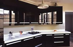 Black kitchen. A small space needn't be white to be light and bright - you can choose black units, but go for black gloss and/or glazed wall units. Corian