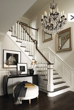 Elegant entry - white trim, dark wood floors, chandelier, crown molding, entryway table and ottoman