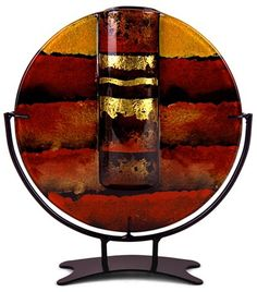 This Contemporary Column, 8inch round bud vase in fused glass is a study in red and orange with black frames and hand painted metallic gold details. Stand included