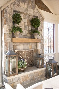 This OUTDOOR FIREPLACE is housed in a screened-in porch, and look how awesome the stonework is! I also like the ivy plants in pots that match the fireplace, as well as the metal/glass lanterns. Very tasteful.