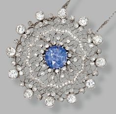 PLATINUM, SAPPHIRE AND DIAMOND PENDANT-BROOCH AND CHAIN, CIRCA 1910    The circular pendant of openwork design set in the center with a round sapphire of violetish blue color weighing 5.86 carats, framed by old European-cut, single-cut and rose-cut diamonds weighing approximately 5.00 carats, together with a platinum link chain, length 24¼ inches.