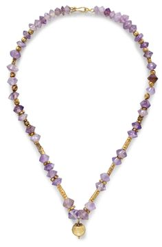 A ROMAN GOLD AND AMETHYST BEAD NECKLACE CIRCA 1ST CENTURY B.C.-1ST CENTURY A.D. Composed of biconical amethyst beads, graduated in size, the upper section interspersed with spherical gold beads, the lower with barrel-shaped gold beads, centered by a lentoid pendant, its loop bifurcating into volutes, punctuated with granules, a cluster of granules at the base; now arranged with a modern clasp, 16-1/4 in. (41.3 cm.) long