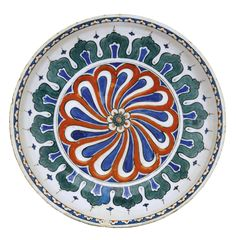 AN IZNIK POLYCHROME POTTERY DISH, TURKEY, CIRCA 1575-80 of rounded rimless form, decorated in underglaze cobalt blue, green and relief red with an abstract design featuring a central rosette with extended petals, bordered by arched panels, with a row of split flowerheads near rim, exterior with stylised cloud bands and floral motifs 28.5cm. diam.
