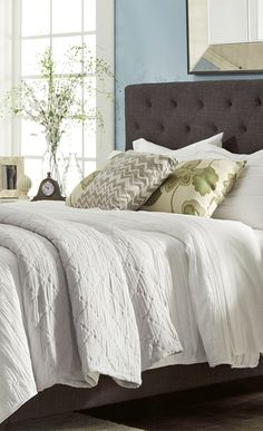An elegant addition to your master suite, this beautiful bed showcases a high-arched headboard and grey-hued upholstery. Update your bedroom at jossandmain.com