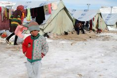 A Syrian child stands in the snow.