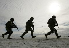 Iraq war Soldiers from the 1st Infantry Division run across a frozen prairie as they train at Fort Riley, Kansas, Wednesday, Jan. 17, 2007. The soldiers from the division's fourth brigade will deploy to Iraq in the next few weeks as part of President Bush's planned troop surge. (AP Photo/Charlie Riedel)