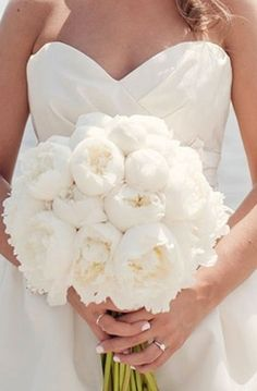 Opt for colorful bouquets for your bridesmaids if yours is all white, like this full bouquet of peonies.