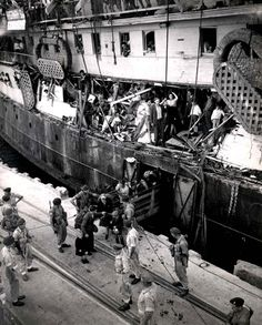 British soldiers removing Jews from the Exodus in the Port of Haifa    Featured here is the Exodus at port in Haifa on July 18, 1947, with the gaping holes in the ship from the ramming of British destroyers; British soldiers are removing the immigrants from the ship. Pictured below are some of the passengers from the Exodus praying aboard the deportation ship Empire Rival during its journey back to France on Tisha Ba'av (the traditional Jewish day of mourning), July 27, 1947.