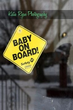 Pregnancy announcement. Photo of mum & dad to be holding the baby on board sign