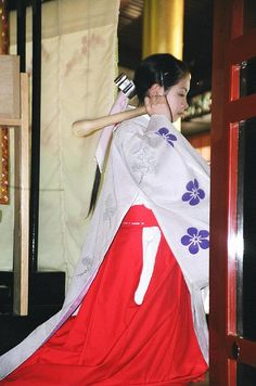 A shrine maiden at a Japanese shrine. She is dressed in junihitoe
