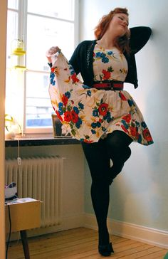 Bright vintage floral dress / large black and red belt / waist length, long sleeved cardigan / black tights / black heels