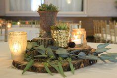 Centerpieces of wood slices votives, succulents, and eucalyptus.