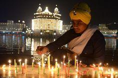Indian Sikh devotees lighting candles during Bandi Chhor Divas, or Diwali, at the Golden T...