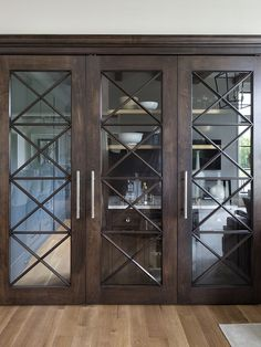 Walnut Glass Inset Doors Custom Walnut doors with glass X insets conceal the butler's pantry and a wet bar