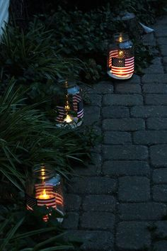 US Flags on glass jars filled with candles light the pathway. #Lighting