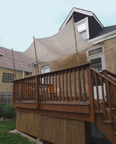 DIY deck shade (about $50).  Materials: Cotton painter's dropcloth, 3 galvanized steel buckets filled with sand, 3 8' bamboo poles, eyebolts, carabiner clips, nylon rope, cleats.