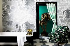 Glamorous bathroom with a tub, printed armchair, and cloud wallpaper