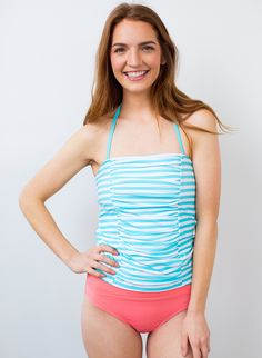 We designed this new Bandeau Pool Stripe Tankini Top just for you! We are loving the stripe pattern... With adjustable straps, gold hardware, ruching, princess seaming, and built-in bra with cups, this suit will be your new favorite!