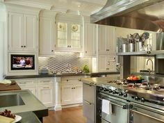 White cabinetry, embedded TV, large stainless island with commercial cooking appliances