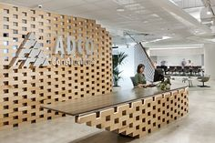 One highly considered design feature expresses ADCO's approach to craftsmanship and materials and fosters company culture. Office Reception Design, Modern Reception Desk, Office Table Design, Reception Counter, Office Interior Design, Office Interiors, Office Decor, Reception Areas, Modern Interior