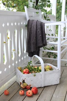 Love the white porch and railings and white cane basket filled with apples.....jeje