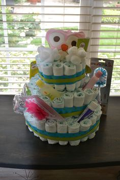 Diaper Cake for baby shower. empty paper towel tube in center. Open each diaper & Roll front to back, secure in center w/one rubber band. Place around toilet paper roll and secure w/LARGE rubber band around the circumference of each layer. Super glue ribbon (DO NOT USE HOT GLUE) around the whole layer to hide ruber bands. Decorate with small items from registry. Bottom layer has 5 rows of diapers, middle has 4 rows, top has 3 rows. #imadethis, #kunwarmade, #partyplanning, #DIY