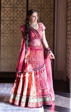 A multi coloured Lehenga with vibrant thread and mirror work by Tarun Tahiliani for the Mehendi of Payal Shah of WeddingSutra.